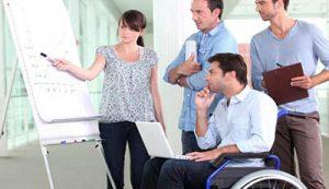 Zdjęcie przedstawia grupę osób wśród których znajduję się osoba z niepełnosprawnością ruchową  biorących udział w warsztatach.
