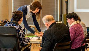 Zdjęcie przedstawia osoby siedzące przy stole, które uczestniczą w warsztatach ścieżki animacji i włączenia społecznego
