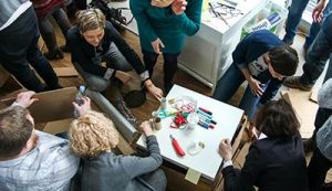 Zdjęcie przedstawia grupę osób biorących udział w warsztatach artystyczno-plastycznych.