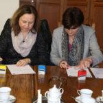 Zdjęcie przedstawia dwie kobiety podpisujące umowę.