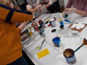 Zdjęcie przedstawia stół z farbami oraz osoby malujące swoje obrazy.