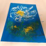Zdjęcie przedstawia obraz namalowany podczas warsztatów. Obraz przedstawia biało-zółty kwiat na niebieskim tle.