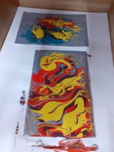 Zdjęcie przedstawia dwa obrazy namalowane podczas warsztatów. Obrazy przedstawiają kolorowe abstrakcję.