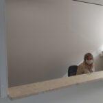 Zdjęcie przedstawia kobietę siedzącą za kontuarem w recepcji, w maseczce ochronnej.