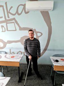 Zdjęcie przedstawia młodego mężczyznę stojącego pomiędzy dwoma biurkami.