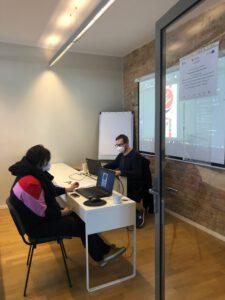Zdjęcie przedstawia dwie osoby siedzące przy biurku w trakcie rozmowy/konsultacji.