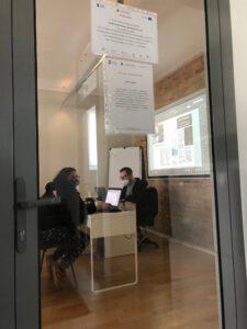 Zdjęcie przedstawia dwie osoby siedzące przy biurku podczas konsultacji za zamkniętymi szklanymi  drzwiami.