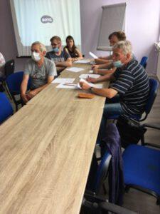 Zdjęcie przedstawia uczestników warsztatów siedzących przy stole.