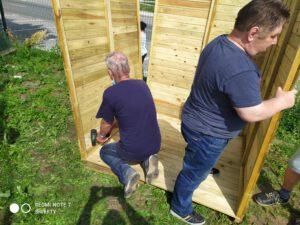Zdjęcie przedstawia mężczyzn montujących ścianki domku narzędziowego