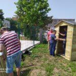 Zdjęcie przedstawia mężczyzn pracujących przy budowie domku.