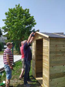Zdjęcie przedstawia mężczyzn montujących dach domku