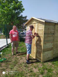Zdjęcie przedstawia mężczyzn montujących drzwi do domku narzędziowego