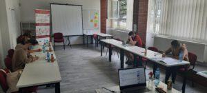 Zdjęcie przedstawia uczestników warsztatu siedzących przy stole w sali warsztatowej.
